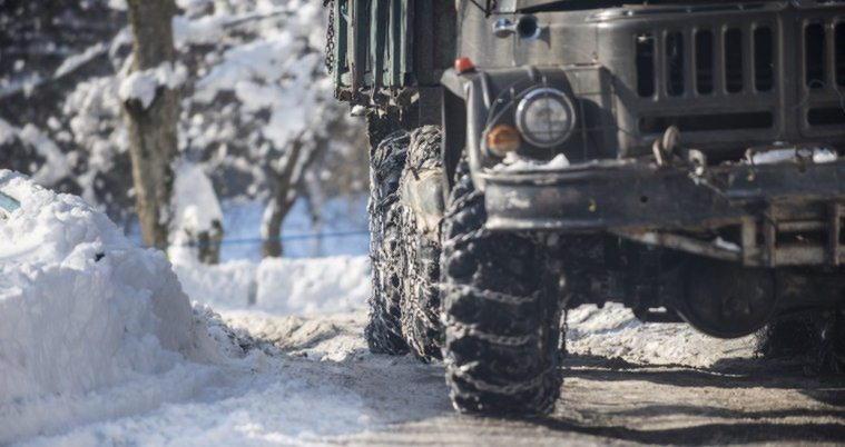 Полноприводный грузовик с цепями противоскольжения при подъеме в гору
