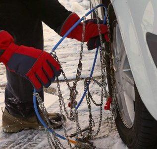 Водитель монтирует цепь на колесо